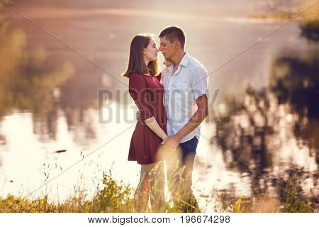 Portrait of a beautiful young couple in love standing and kissing near the river.