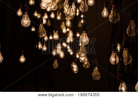 Art installation consisting of a perspective of hanging tungsten lamps at the Cochin art festival Kerala India.