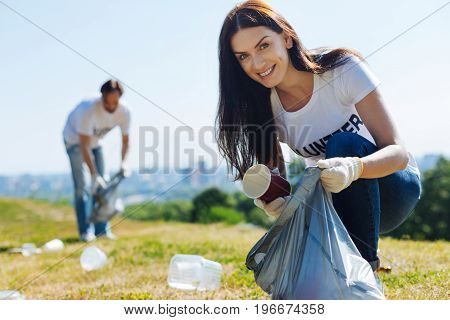 Improving the world. Clever energetic sincere lady taking care of the environment and participating in eco campaign while cleaning local park from garbage