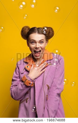 Girl with hairbuns wearing purple jacket with orange collar holding hand on chest and soap bubbles.