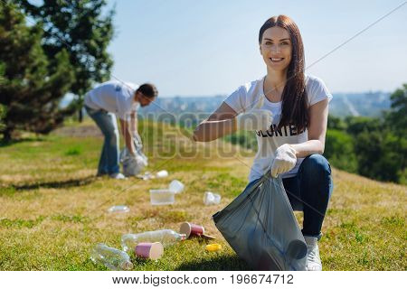 Protecting the nature. Productive motivated bright woman running a campaign promoting eco friendly way of life while participating as a volunteer an cleaning the litter