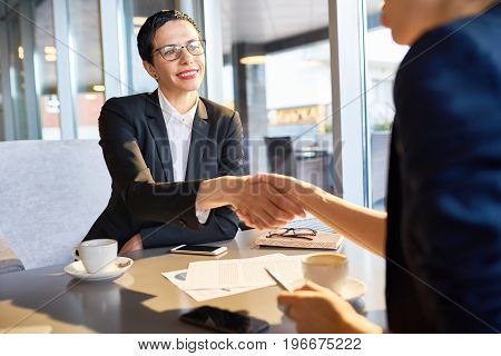 Portrait of confident female leader smiling happily while shaking hand of unrecognizable business partner during work meeting in cafe