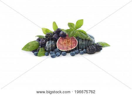 Group of fresh fruits and berries with basil's on a white background. Ripe blueberries blackberries grapes plums and figs. Blue and purple food. Fruits with copy space for text.