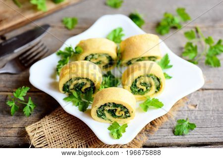 Appetizing omelette rolls with cheese and greens on a white plate and a vintage wooden table. Stuffed sliced omelette recipe idea. Country style