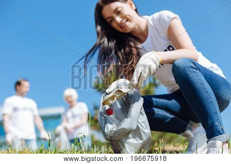 Saving what saves us. Persistent capable intelligent woman picking up litter and putting in plastic bags while participating in eco campaign