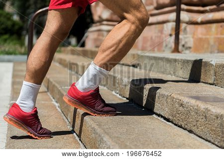 Close up of muscular legs of young athlete going up stone ladder with handrail. He is wearing training shoes and socks