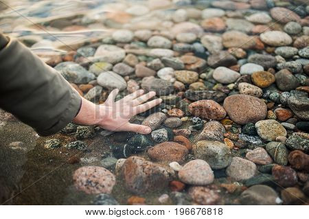 Hand in the clear water of the lake. Seen many stones on the bottom