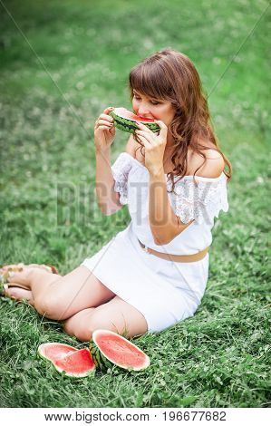 Young Beautiful Woman Sitting On The Grass And Eat Watermelon. Happy Girl Resting On The Grass. Warm