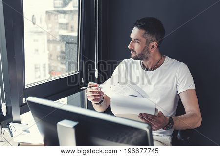 Rainy day. Stylish bristled adult man in casual clothes is sitting at table with documents while looking through window thoughtfully