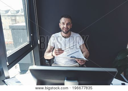 Positive and successful. Fashionable cheerful manager is working with papers while looking at camera with joy. He is laboring in modern office