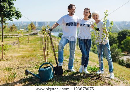 Changing the planet. Diligent open minded hardworking citizens posing on a lawn where they planting new trees and working for the sake of healthy future and environment