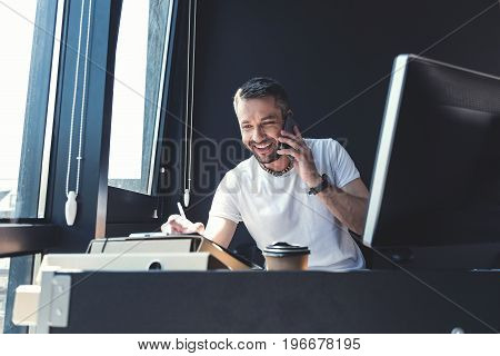 Good deal. Cheerful adult worker with stubble is enjoying conversation on mobile phone and smiling while making some notes. He is sitting at table with computer in modern office