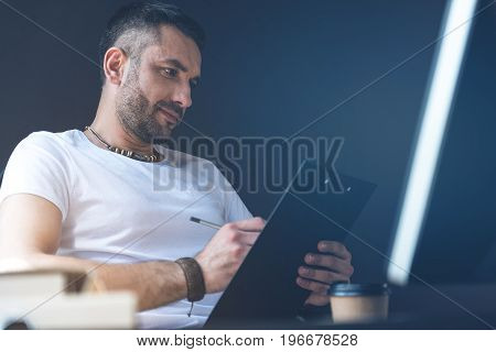 Important tasks. Low angle of pleasant bristled manager is sitting at desk and holding folder with documents and pen. He is making some marks with concentration. Copy space in the right side