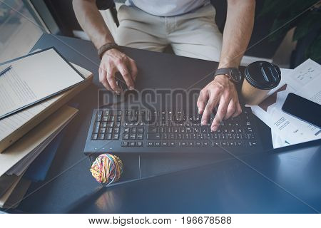 Do it immediately. Close up top view of hands of competent manager is holding mouse in right hand and typing text while using keyboard of his computer