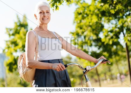 Active weekends. Positive female person putting hands on the handle bar and having backpack on right shoulder while looking straight at camera
