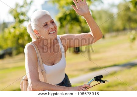Hey you. Positive delighted mature woman keeping smile on her face and looking forward while riding bicycle