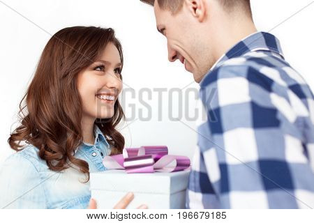 Side view of young smiling couple exchanging gift on white background.