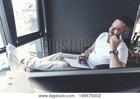 Work with pleasure. Glad mature man is resting in his chair while having pleasant conversation on phone. He is putting his legs up on his desk and making some notes with smile. Copy space in left side