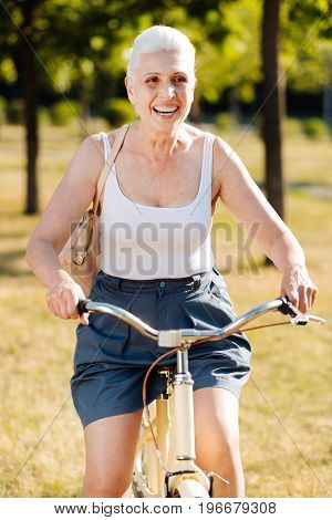 Happy day. Positive female person sitting on her transport and putting hands on handle bar while keeping smile on her face