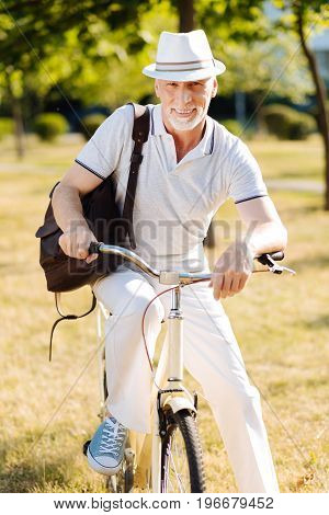 Stylish pensioner. Delighted male person wearing hat and putting hands on handle bar while posing on his bicycle