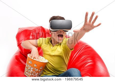 Little boy sitting on chair in VR headset and eating popcorn.