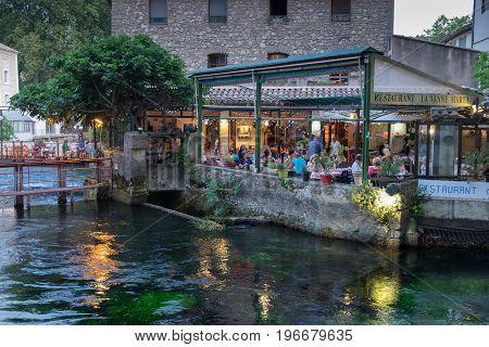 FONTAINE-DE-VAUCLUSE FRANCE - JUNE 21 2017: An picturesque restaurant on water at Fontaine-de-Vaucluse