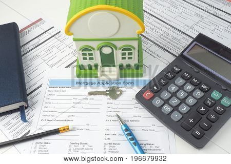Mortgage application form top view house model notebook calculator pen pencil and key business mortgage concept