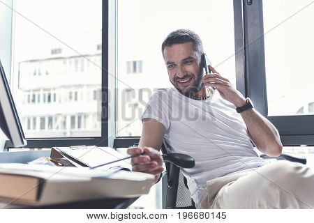 Pleasant communication. Happy bearded relaxed manager is having conversation on mobile phone while sitting at desk and expressing gladness. Selective focus and copy space in the left side