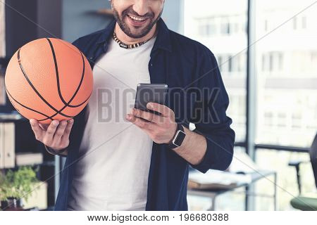 Love my hobby. Close-up of ball in hand of joyful bristled mature man, which is typing on mobile phone with smile while standing in his office