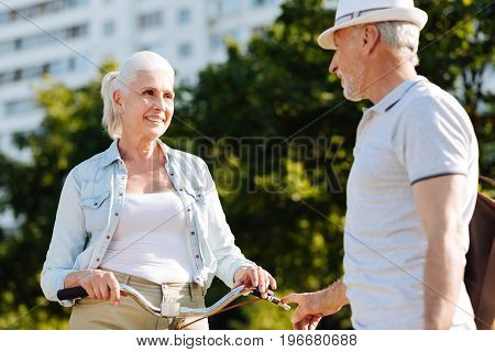 Nice to meet you. Charming female person putting hands on handle bar while standing opposite her husband and looking into his eyes