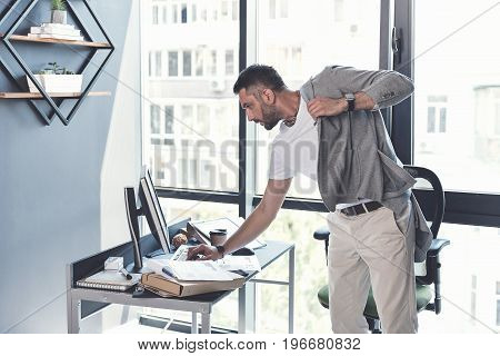 Hurry up. Modish man is typing on keyboard, looking at display with concentration while standing near his workplace in modern office, and dressing his jacket. Copy space in the left side