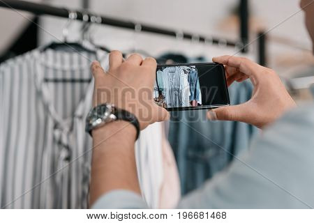 Close-up Partial View Of Young Man Photographing Clothes With Smartphone