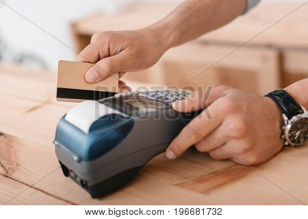 Close-up Partial View Of Man Making Payment By Credit Card And Terminal