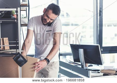 Make it all in time. Positive adult energetic worker is taking folder with documents while talking on mobile phone with smile. He is standing in modern office. Copy space in the right side