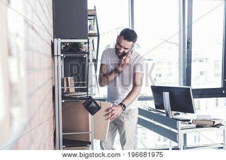 Multifunctional job. Joyful mature worker is standing in cozy office and taking folder with documents while having pleasant conversation on smartphone. Big window on background