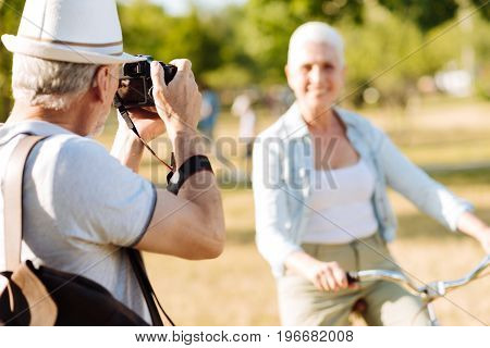Keep smiling. Attentive mature man holding camera in both hands and standing in semi position opposite his model
