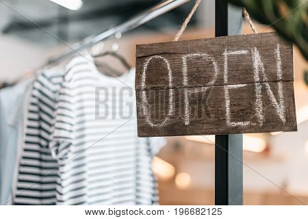 Close-up View Of Wooden Sign Open Hanging In Boutique