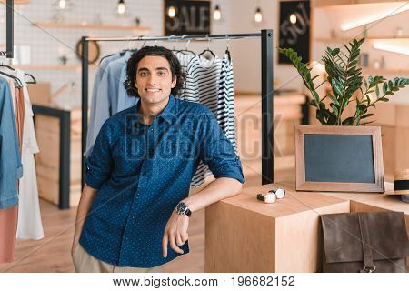 Handsome Young Man Standing And Smiling At Camera In Boutique