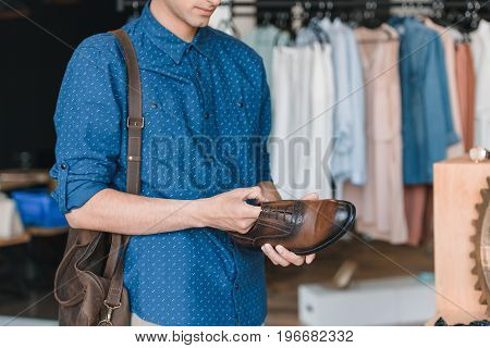 Cropped Shot Of Young Man Holding Shoe While Shopping In Boutique