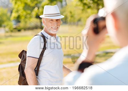 My love. Friendly man showing his smile and keeping backpack on shoulders while posing on camera