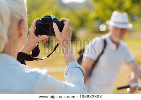 I am photographer. Silhouette of strong man that standing on the background and looking forward while standing opposite his woman