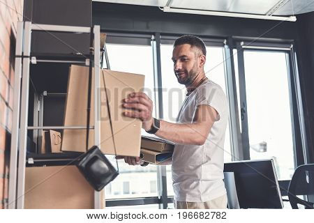 Much work. Low angle of pleasant man is taking folders with documents from shelf while standing in modern office