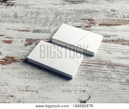 Blank business cards on light wood background. Template for ID. Mock up for branding identity.