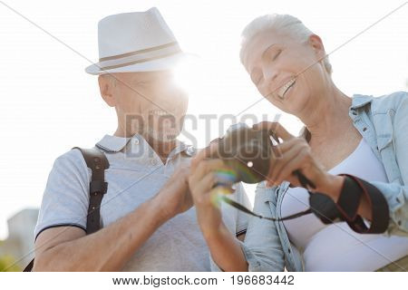 Positive memories. Smiling woman holding camera in both hands and looking downwards while showing pictures to her man