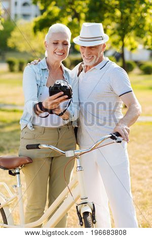 Happy people. Handsome man embracing his wife and putting left hand on the handle bar while looking at photo camera