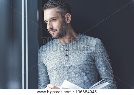 Feeling inspired. Portrait of attractive man is leaning on window and looking through glass thoughtfully while holding book