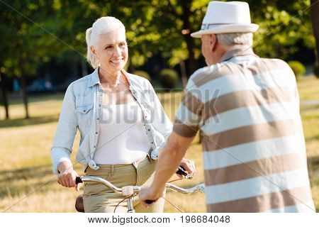 Pleasant conversation. Positive blonde keeping smile on her face and sitting on the bicycle while holding handle bar