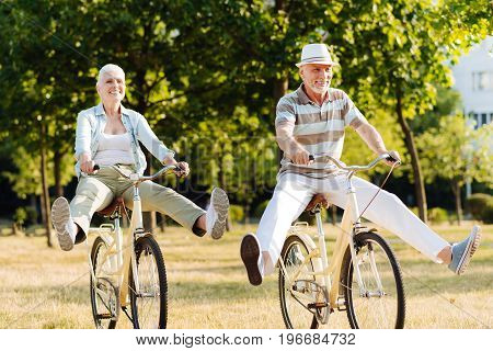 Like little children. Positive male person holding handle bar and keeping smile on his face while looking forward