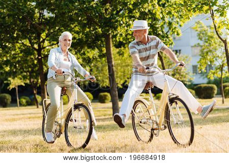 Lets have a rest. Joyful male person keeping both legs in the air while turning head to his wife and keeping smile on his face