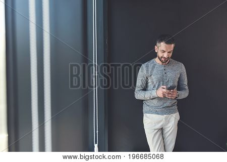 Sharing info with colleagues. Elegant adult manager wearing casual clothes is looking at screen of his smartphone while leaning on gray wall. Copy space in the left side